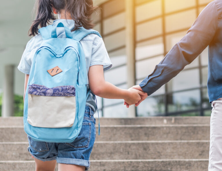 Student walking up school steps with backpack
