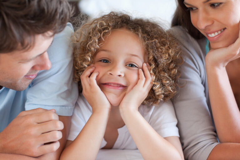 Child with parents smiling