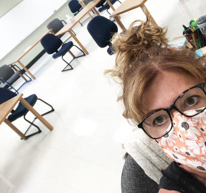 Teacher wearing mask in empty classroom