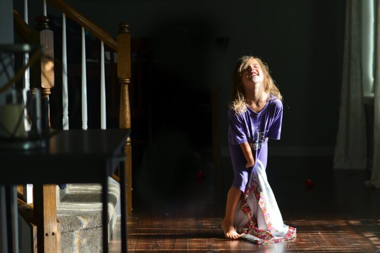 Little girl laughing by staircase