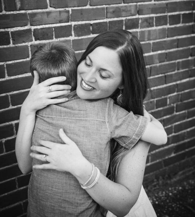 Mother hugging her young son, black-and-white photo