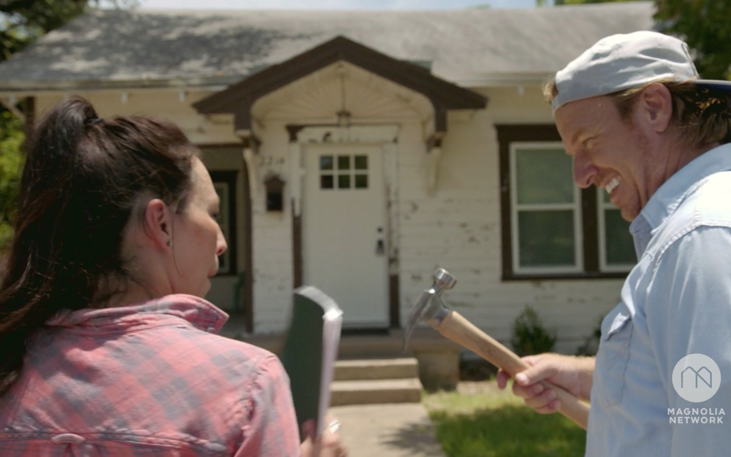 Chip and Joanna Gaines in front of Fixer Upper house