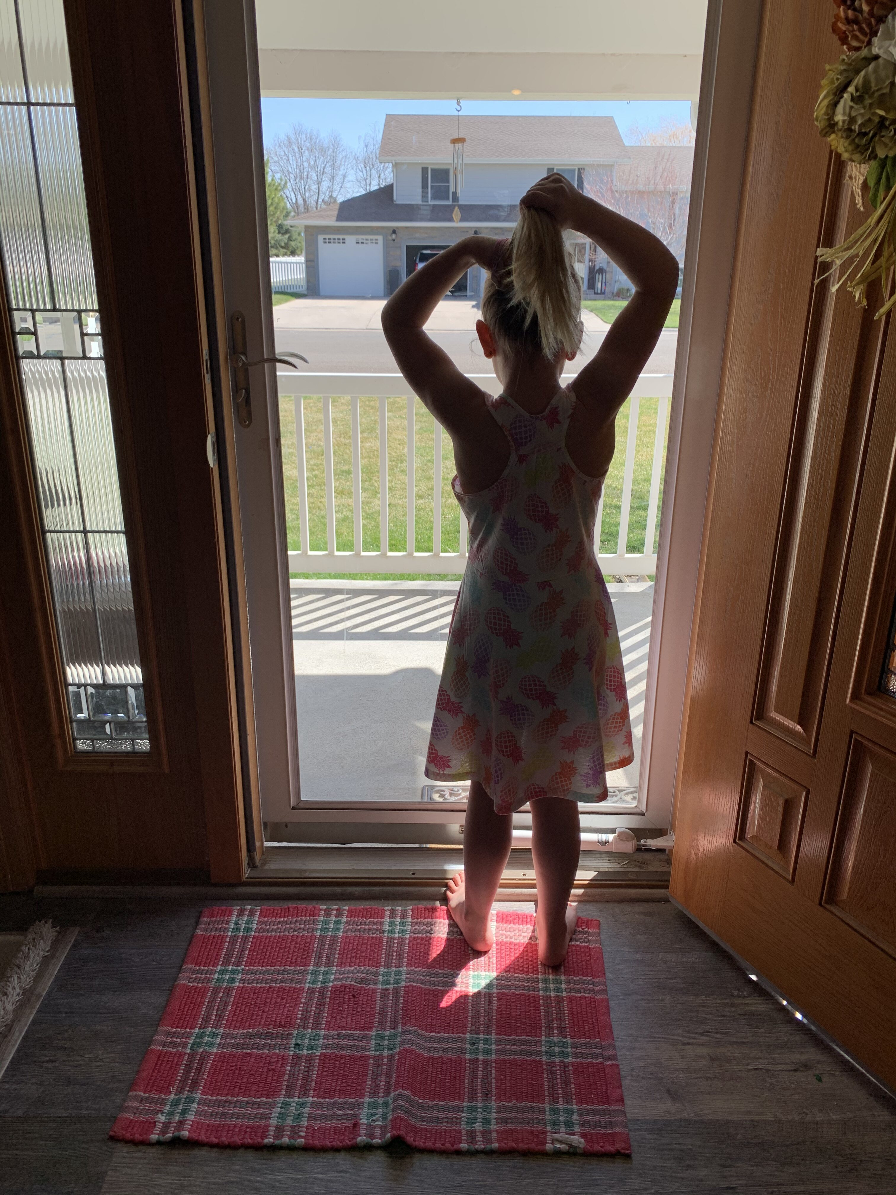 Little girl looking out front door, color photo
