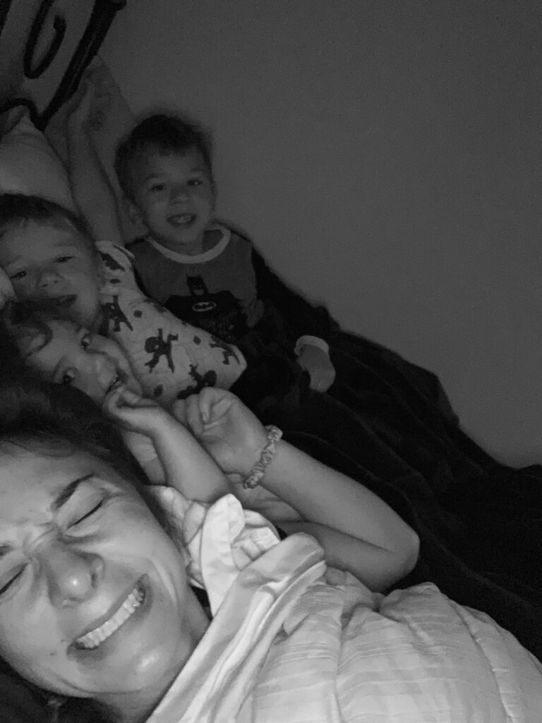 Mother in bed with three children, black-and-white photo