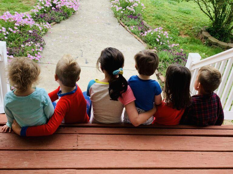 Children sitting on porch steps, color photo