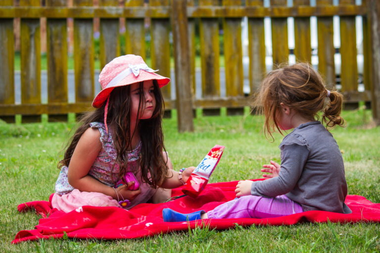Two little girls sitting on blanket outside, color photo