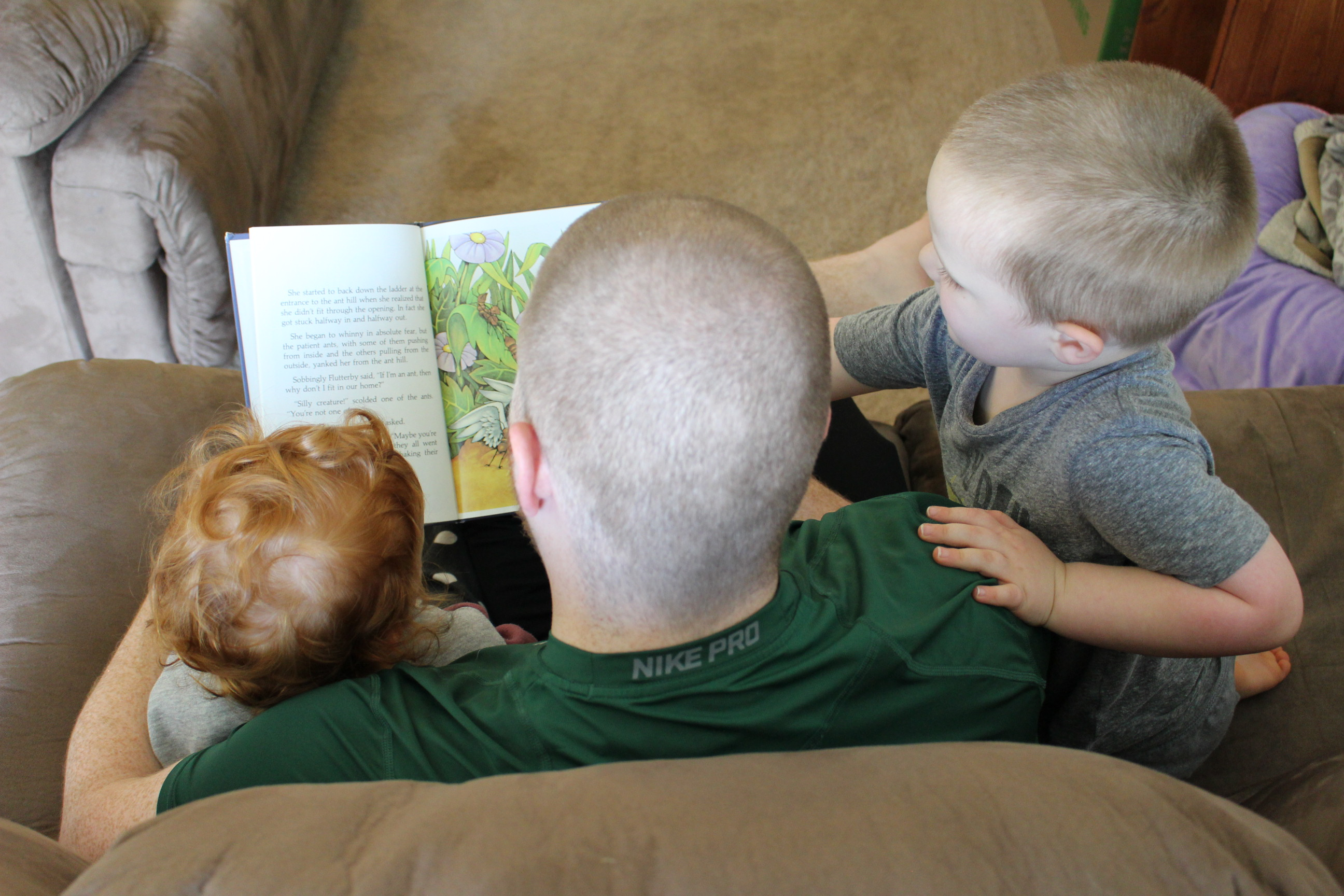 Daddy reading to his children, color photo