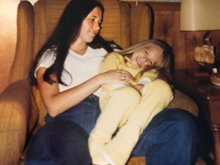 Daughter sitting on mother's lap, color photo
