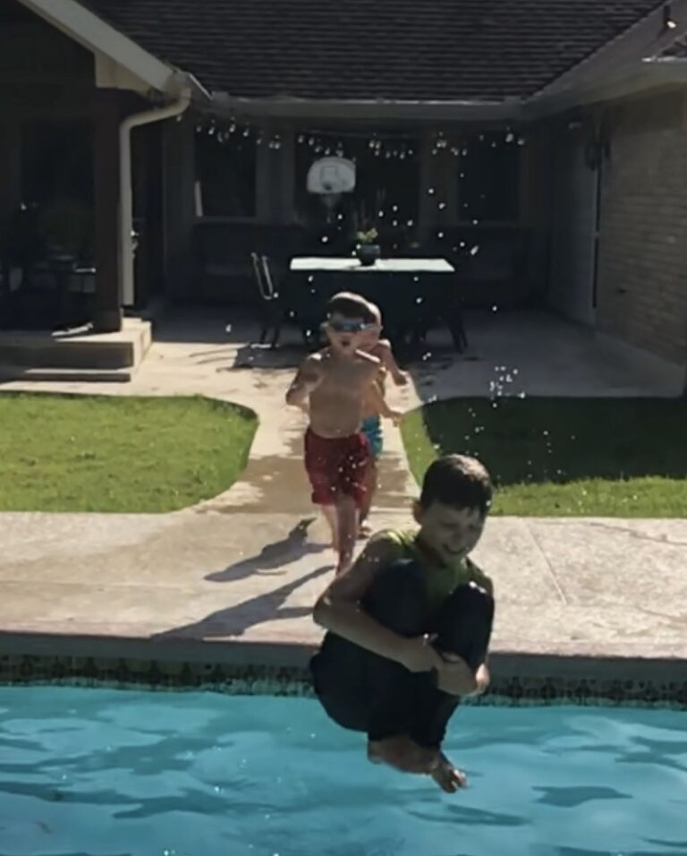 Boys jumping into swimming pool, color photo