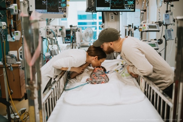 Parents kissing child in hospital bed