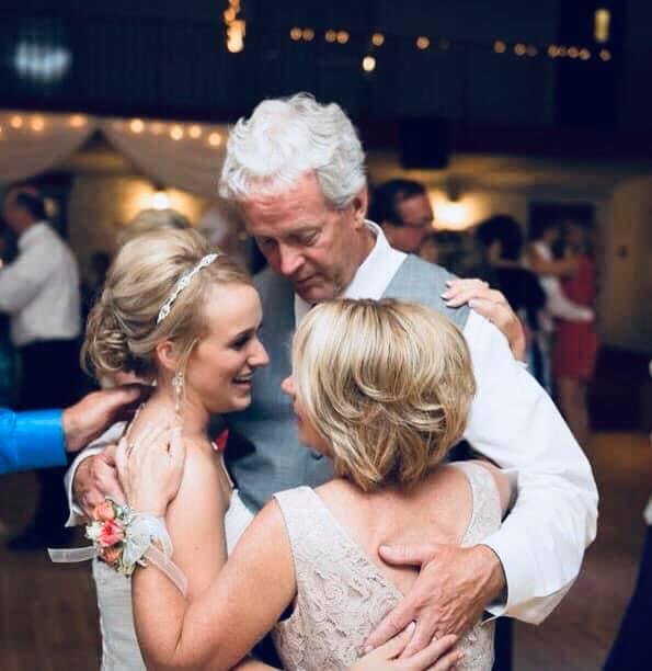 Mom and dad hug bride
