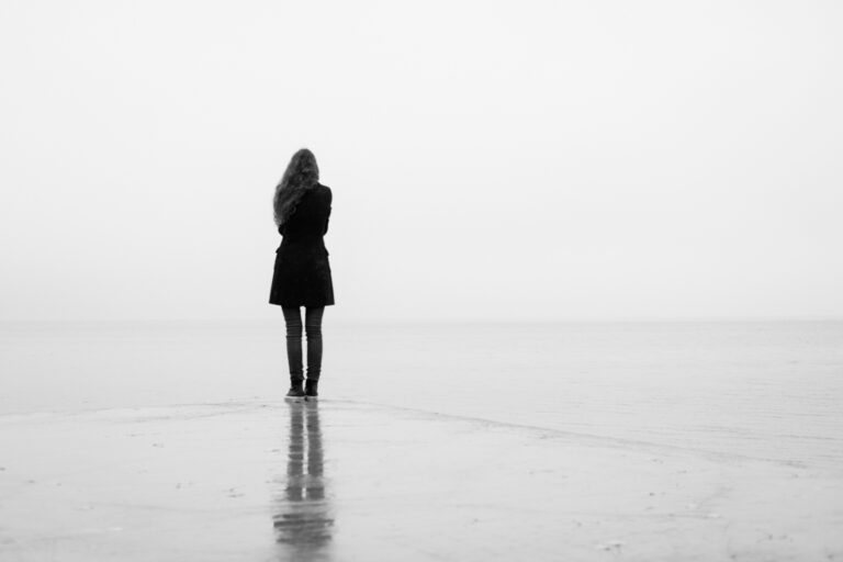Woman standing by foggy water