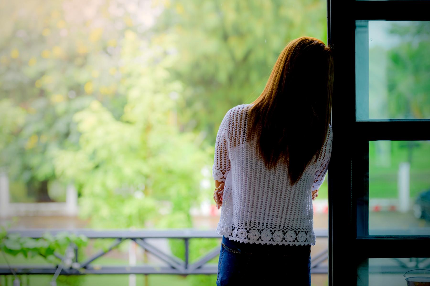Woman leaning against doorway