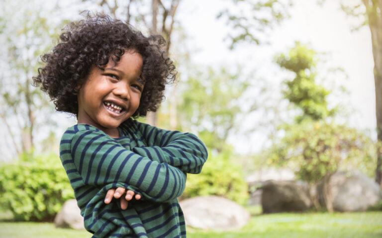 Little boy smiling outside