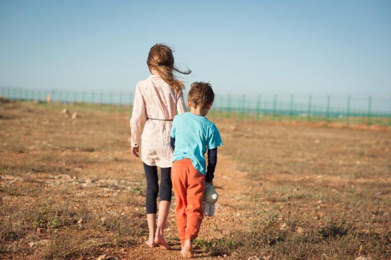 Two kids walking in field