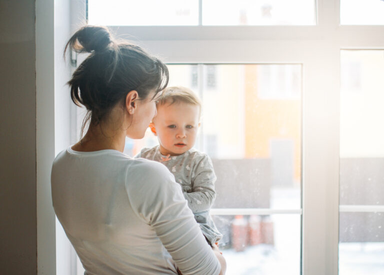 Mom holding toddler by window