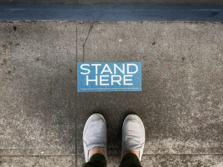 Standing by stand here sign