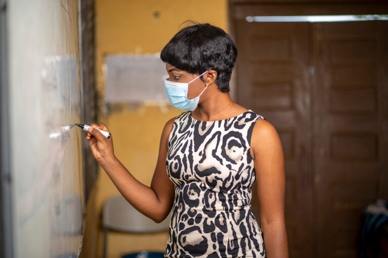 Teacher writing on board with mask