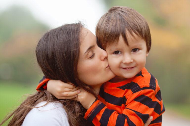 Mom kissing preschool child