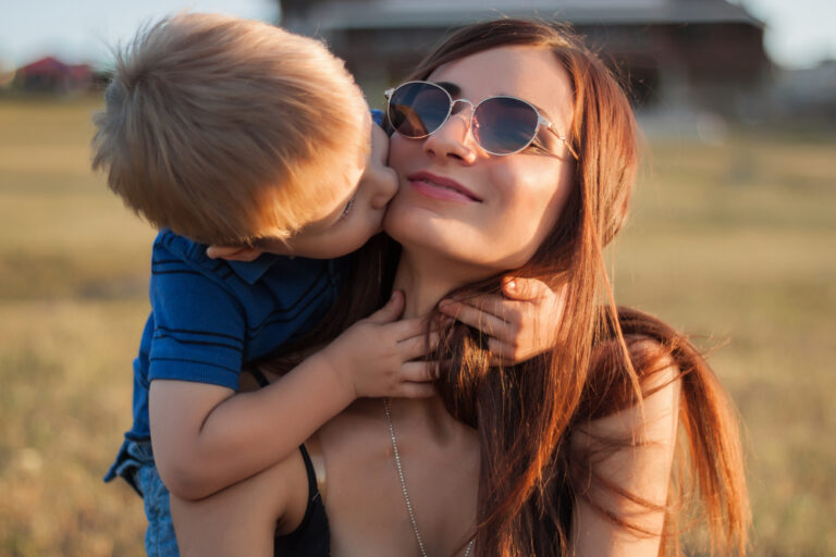 Little boy kissing mother