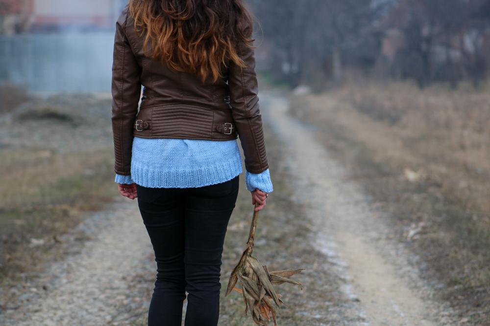 Woman walking down road alone