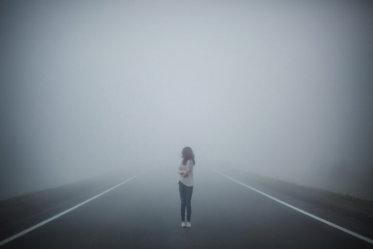 Woman standing on foggy road