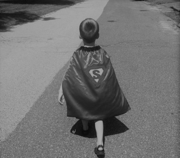 Little boy in a superman cape