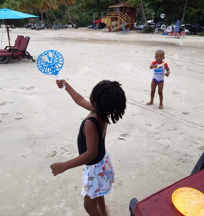 Children playing with bubbles on the beach, color photo