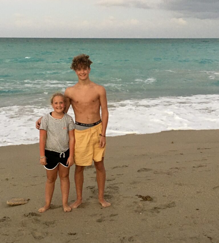 Young man standing with little sister on beach, color photo