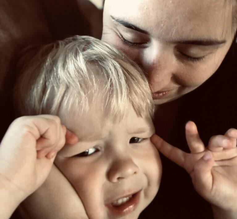 Mother holding upset little boy, color photo