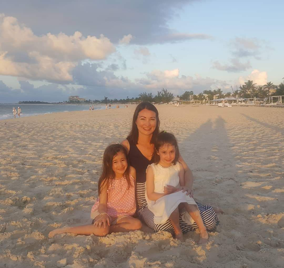 Mother and two daughters on the beach, color photo