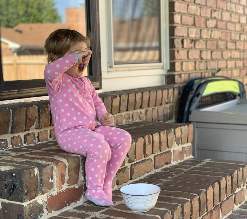 Little girl sitting on steps, color photo