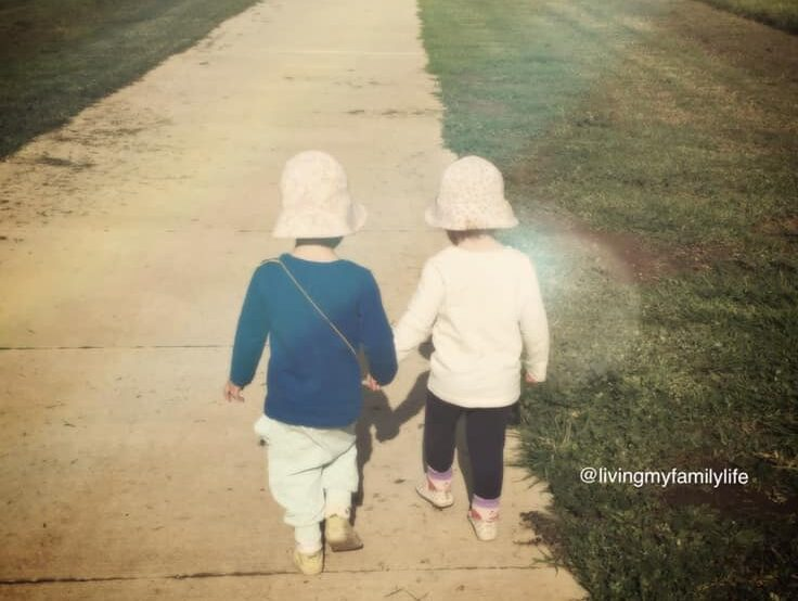 Two children walking hand-in-hand down sidewalk, color photo
