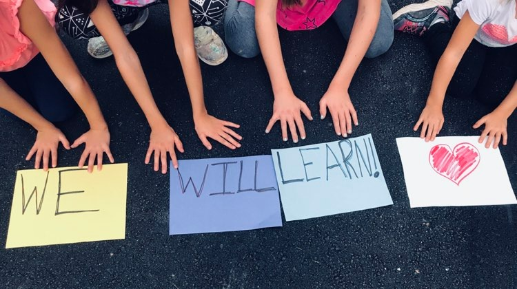 Four children, with signs stating: We Will Learn, color photo