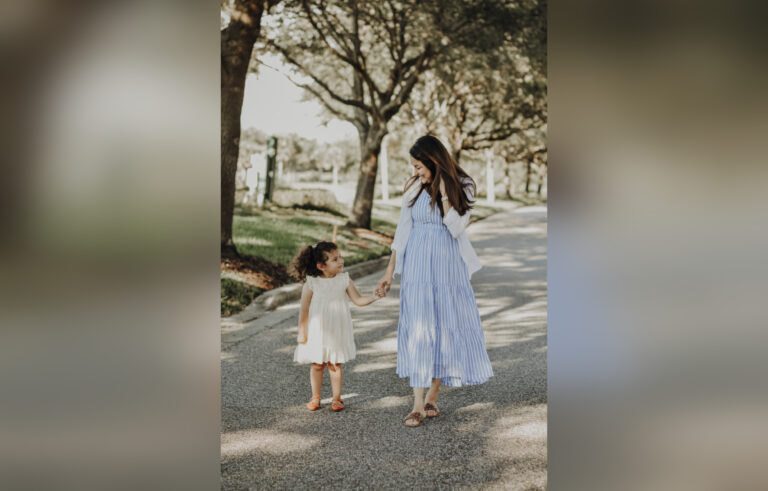 Mother and daughter walking down road
