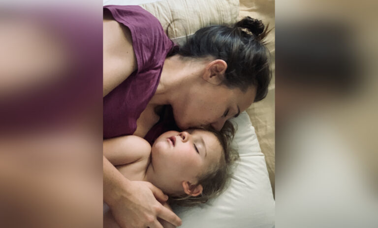 Mother holding sleeping toddler, color photo