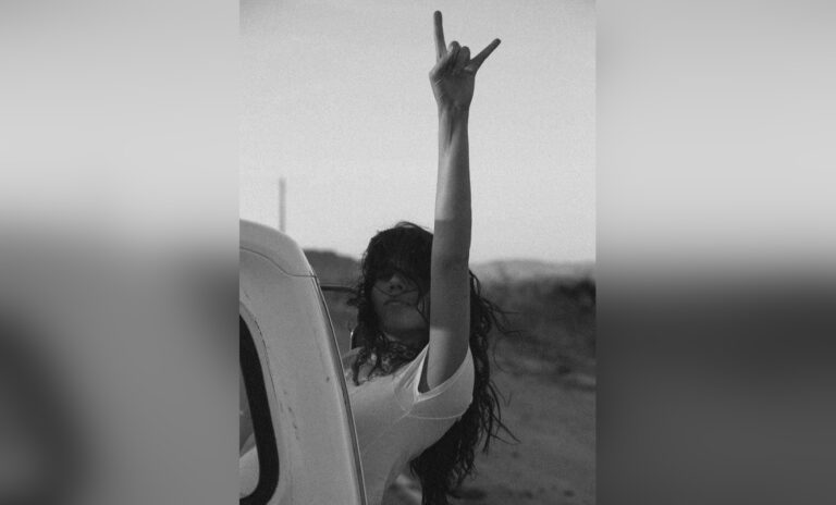 Woman in black and white photo with hand raised