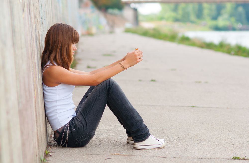 Teen sitting on road alone