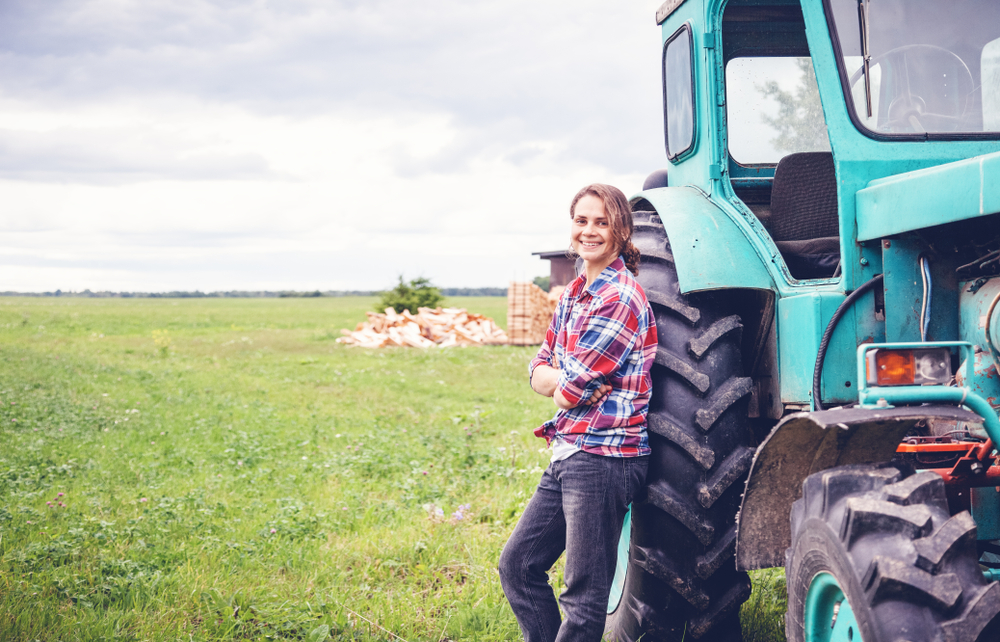 Woman standing by tractor on farm
