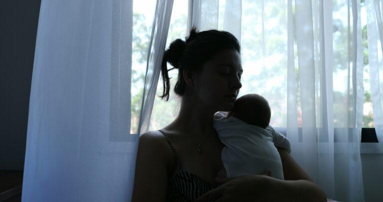 Woman by window with newborn