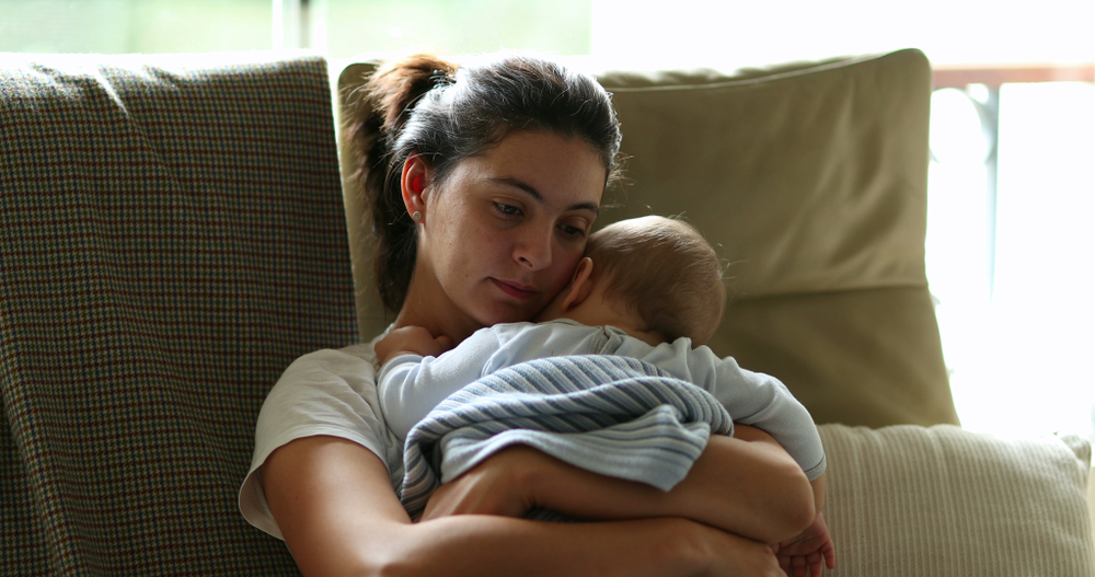 Mom with baby sitting on couch