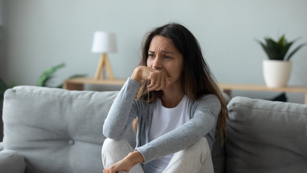 Sad woman sitting on couch