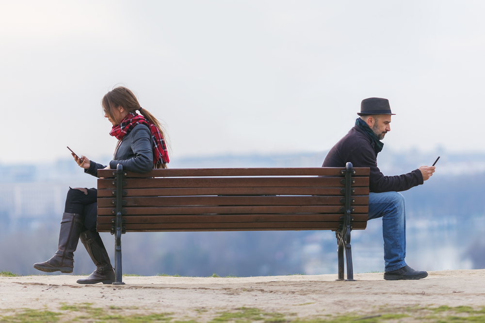 Man and woman on bench with distance