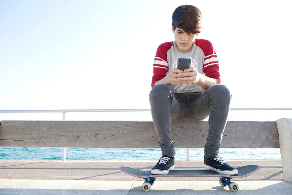Teenage boy sitting with phone