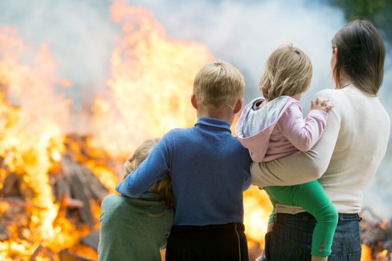Family in front of house fire
