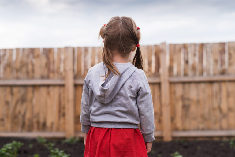 little girl standing outside alone