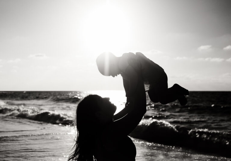 Mother holding up toddler silhouette