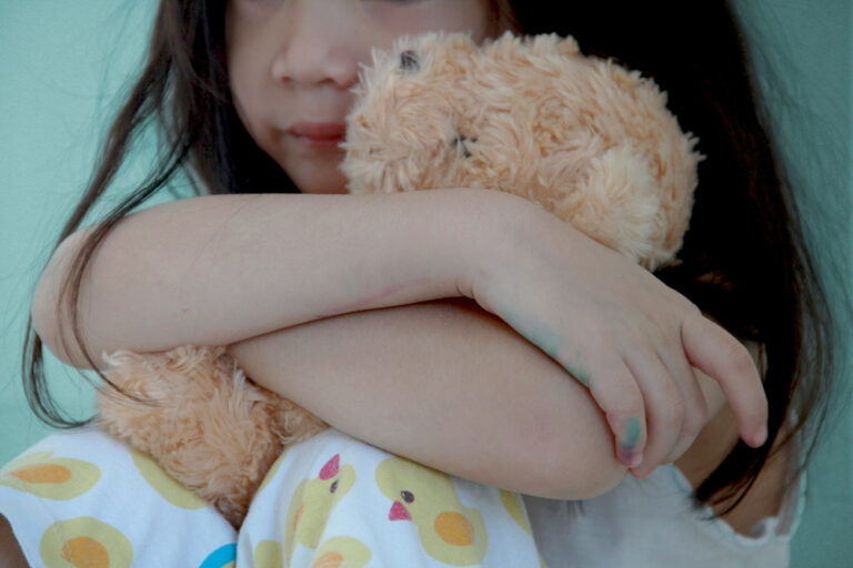 Little girl hugging stuffed bear