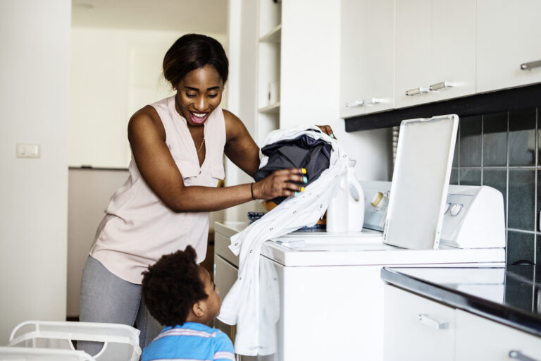Mom doing laundry with child looking on