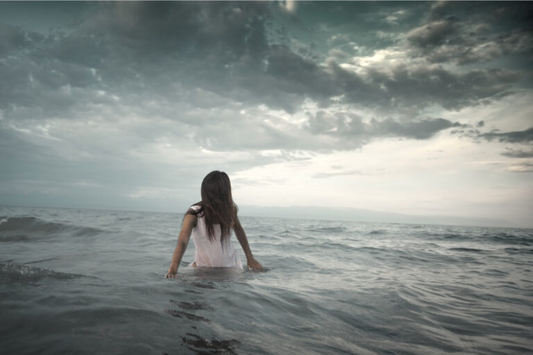 Woman in water with storm in distance